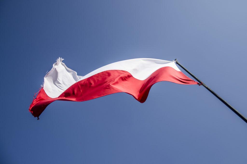 Polska flaga łopocząca na wietrze, symbol odzyskania przez Polskę niepodległości